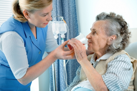 weakness: Nurse cares for a elderly woman lying in bed Stock Photo