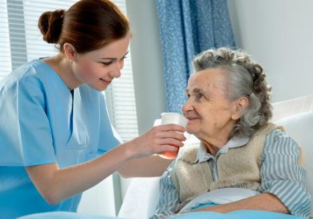 doctor verpleegster: Verpleegster zorgt voor een oudere vrouw die in bed ligt Stockfoto