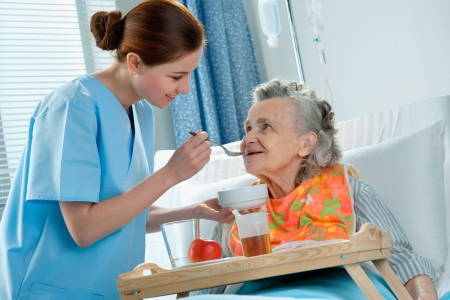 dementia: senior woman 90 years old being fed by a nurse