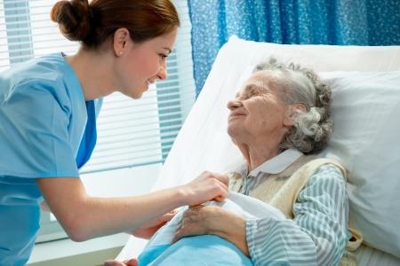 enfermeria: Enfermera atiende a una anciana tumbado en la cama