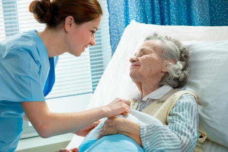 pielęgniarki: PielÄ™gniarka dba dla starszych kobieta leżącego w DNA Zdjęcie Seryjne