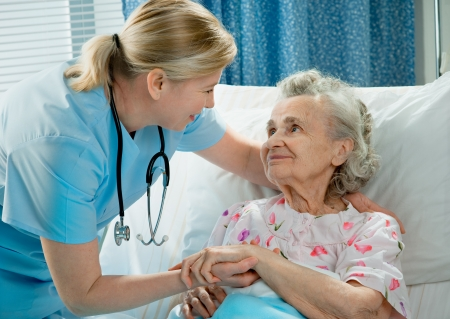 nursing homes: Nurse cares for a elderly woman lying in bed Stock Photo