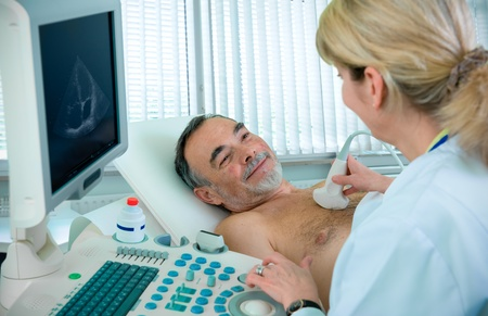 Doctor is using ultrasound machine to scan the heart of a senior male patient Stock Photo