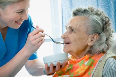 80s adult: mujer Senior 90 a�os siendo alimentado por una enfermera Foto de archivo