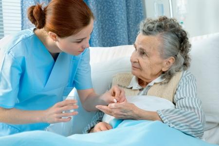 pills in hand: Enfermera atiende a una anciana tumbado en la cama