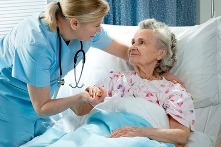 Nurse cares for a elderly woman lying in bed Stock Photo