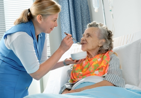 assisted living: senior woman 90 years old being fed by a nurse