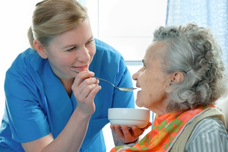senior woman 90 years old being fed by a nurse photo
