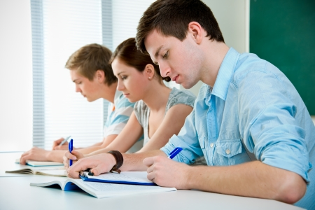 students studying: young students studying together in a classroom