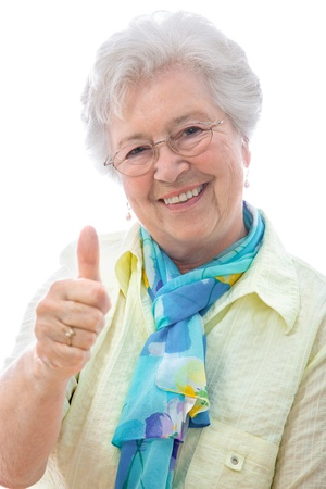 An elderly woman showing thumbs up sign  isolated against white photo