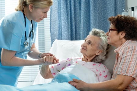 healthcare visitor: Doctor talking to elderly patient lying in bed in hospital