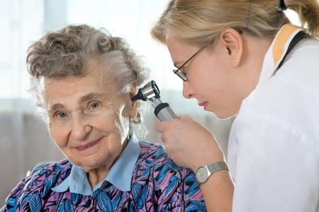 physical test: Medico che esegue esami orecchio con otoscopio su un paziente anziano