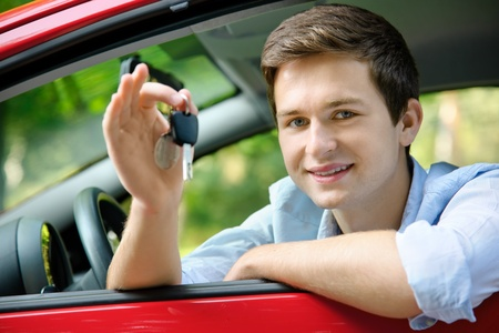 driving school: teenager sitting in new car and shows the keys