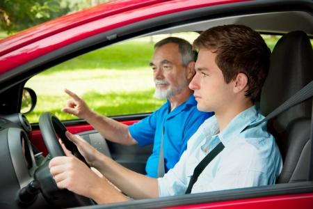 hombre manejando: Adolescente aprendiendo a conducir con su instructor de conducción
