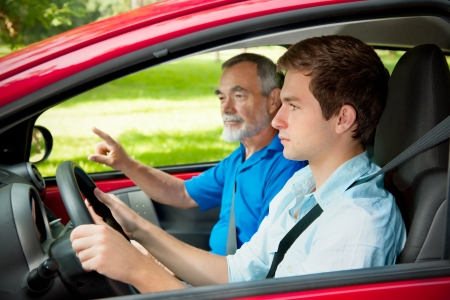Teenager learning to drive with his driving instructor photo