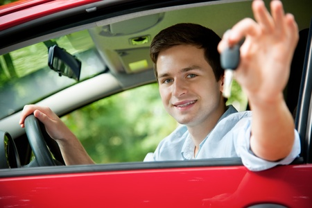 teenager sitting in new car and shows the keys photo