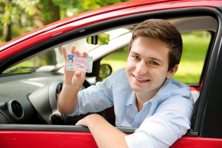 teenager sitting in new car and shows his drivers license photo