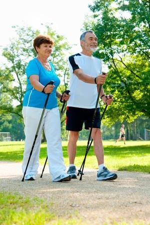 ancianos caminando: Pareja alto n�rdicos paseando por el Parque