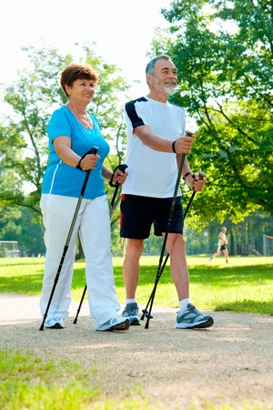 senioren wandelen: Senior paar Nordic walking in het park Stockfoto