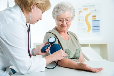 doctor measuring blood pressure of senior woman