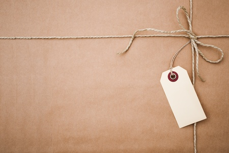 pack string: Brown paper parcel with a blank tag and copy space