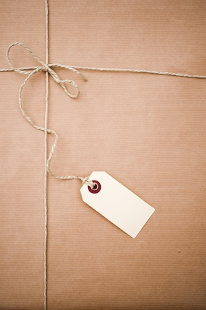tagged: Brown paper parcel with a blank tag and copy space