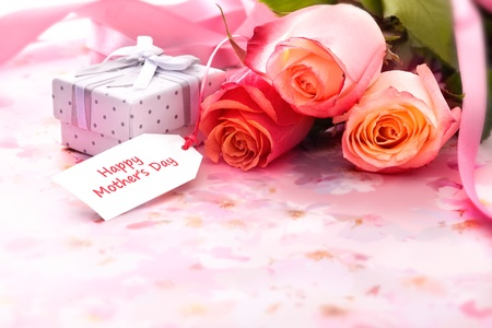 Bouquet of roses and gift box with a mothers day card photo