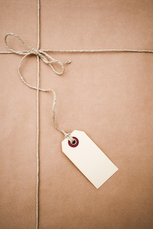 pack string: brown paper parcel with a blank luggage tag Stock Photo