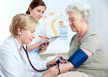 checking: Female doctor measuring blood pressure of senior woman