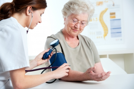 Female doctor measuring blood pressure of senior woman  photo
