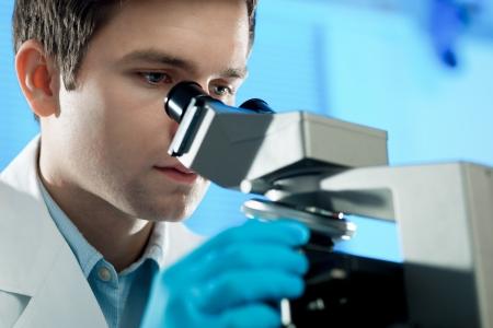 investigador cientifico: Cient�fico se ve en microscopio Foto de archivo