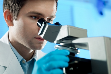 scientific: Scientist looks into microscope