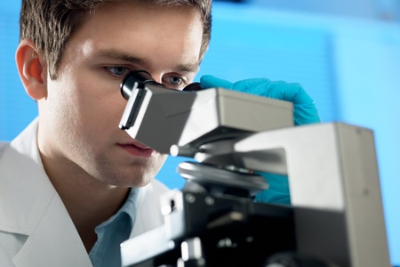Scientist looks into microscope photo