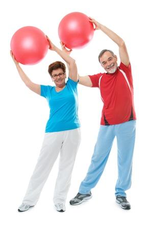 hombres haciendo ejercicio: Matrimonios de edad haciendo ejercicio físico con una pelota en el gimnasio de deporte
