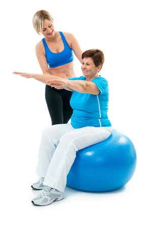 sportwear: Senior woman doing fitness exercise with help of trainer at sport gym
