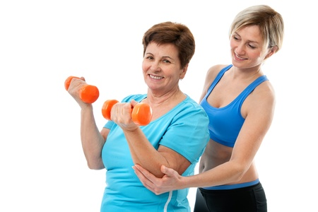 Senior woman doing fitness exercise with help of trainer at sport gym photo