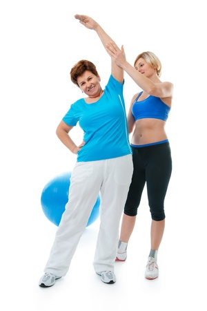 Senior woman doing fitness exercise with help of trainer at sport gym Stock Photo - 12351094