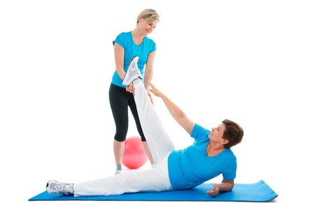 Senior woman doing fitness exercise with help of trainer  photo