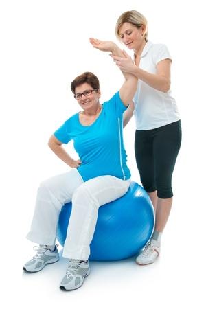 f�sica: Superior de la mujer haciendo ejercicio f�sico con la ayuda de su entrenador en el gimnasio de deporte
