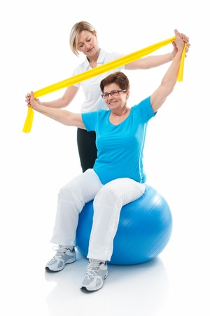 physical: Senior woman doing fitness exercise with help of trainer at sport gym