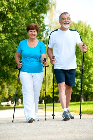 guy with walking stick: senior couple making nordic walking in the park  Stock Photo
