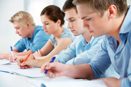 exams: group of students studying together in classroom