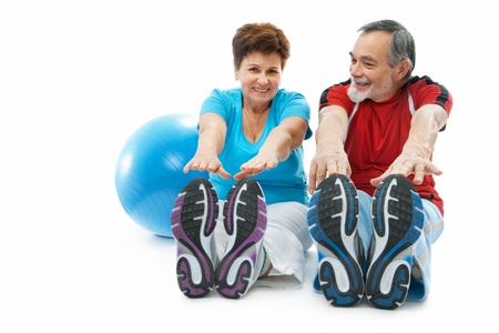 physical training: senior couple doing stretching exercise at the gym