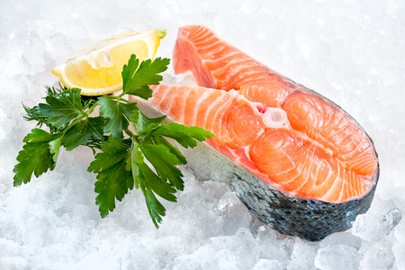 fresh salmon fillet with parsley and lemon slices on ice photo