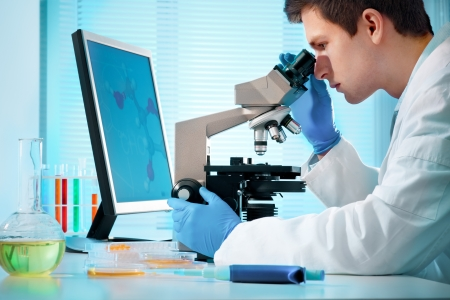 science lab: scientist looking into microscope at the lab Stock Photo
