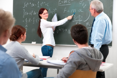 secondary education: teacher with a group of high school students  in classroom