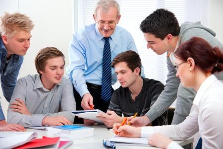 insegnante con un gruppo di studenti delle scuole superiori in aula