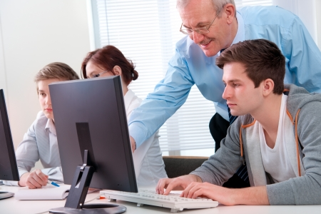 computer training: Students with a teacher in computer classroom
