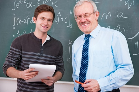 professor: Student  with a teacher at the blackboard  in classroom Stock Photo