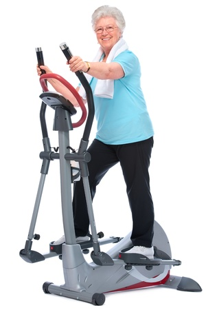 Attractive senior woman at health club, exercising on stepper photo